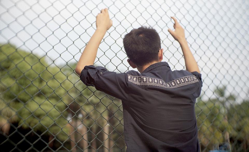 柵につかまり悩む男性