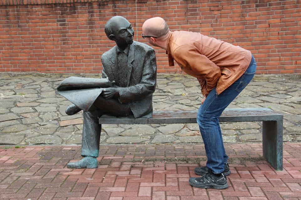 似た銅像を覗き込む男性