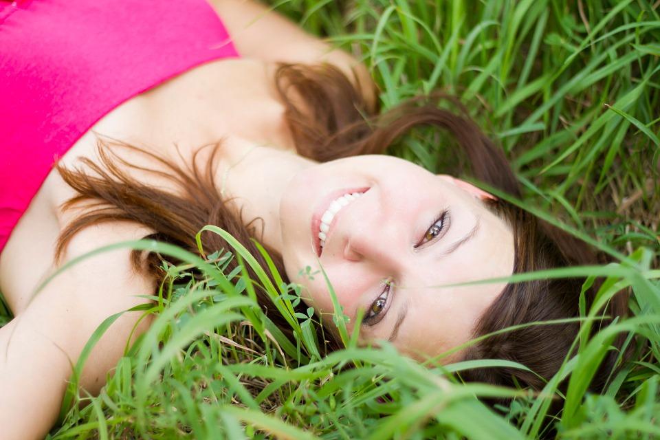 芝生で笑顔な女性