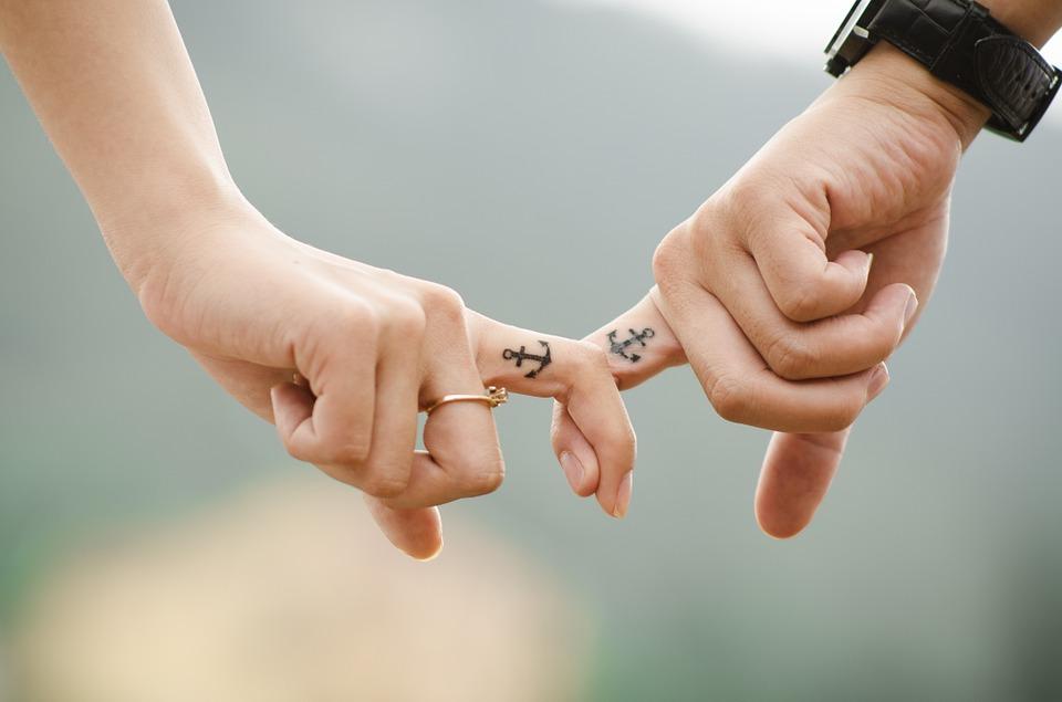 指を絡める男女の手